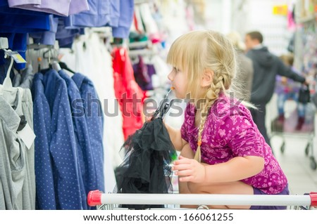 Adorable girl on shopping cart select clothes in supermarket