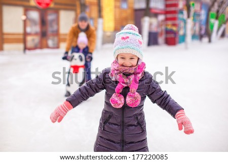 Adorable girl on skating rink, dad with little sister in the background - stock photo