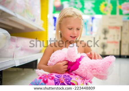 Adorable girl play with plush toy and pillow sitting on floor in department section - stock photo