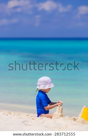 Adorable girl playing with beach toys during tropical vacation - stock photo