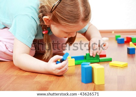 Adorable girl playing with blocks - stock photo