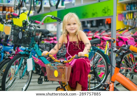 Adorable girl portrait sitting on bicycle in supermarket