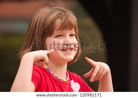 Adorable Girl Poses While Playing Outside. - stock photo