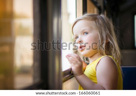 Adorable girl ride by bus and look through open window outside - stock photo