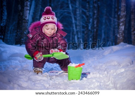 Adorable girl ride on ski and play with snow in evening park - stock photo