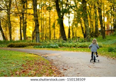 Adorable girl riding a bike on beautiful autumn day - stock photo