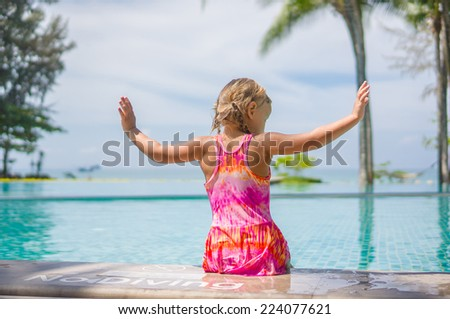 Adorable girl seat at side of swimming pool with legs in water and hand to fly in tropical beach resort with ocean on back - stock photo
