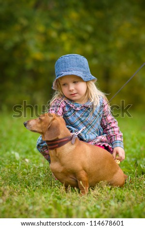 Adorable girl seat near dachshund with collar and leash on grass in park - stock photo
