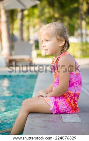 Adorable girl seat on  pool side at tropical beach with legs in water. Chairs and umbrellas on back - stock photo
