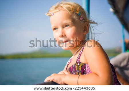 Adorable girl see out to water on upper deck of ferry boat between islands