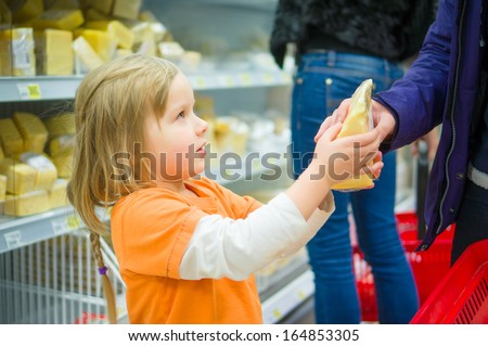 Adorable girl select cheese with mother in supermarket - stock photo