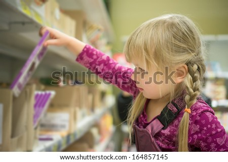 Adorable girl select chocolate bars on shelf in supermarket - stock photo