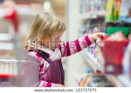 Adorable girl select dolls and toys on shelves in supermarket