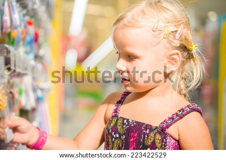 Adorable girl select goods in stationery department in supermarket - stock photo