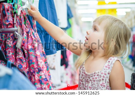 Adorable girl select light dresses in cloth department in supermarket - stock photo