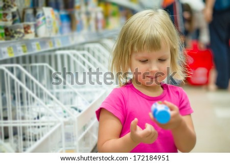 Adorable girl select milk products holding yogurt small bottle in shop