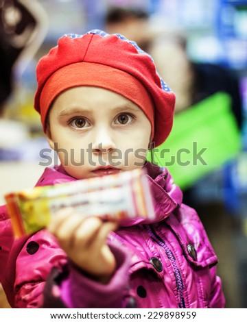 Adorable girl select sweet on shelves in supermarket - stock photo