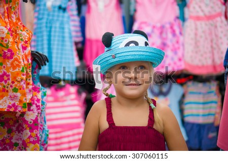 Adorable girl selects blue hat among beautiful baby girl dresses on stands and hangers in supermarket