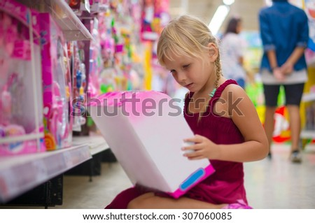 Adorable girl selects blue toy dolls on shelves in supermarket - stock photo