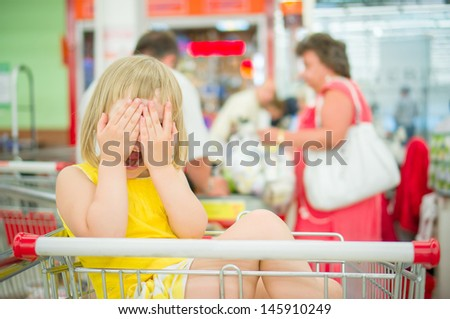 Adorable girl sit in shopping cart and close face with hands near cash desk - stock photo