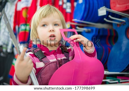 Adorable girl sit on shopping cart with pink sled and brushes and paints in hands in supermarket