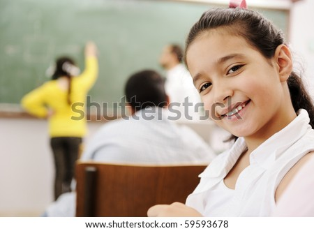 Adorable girl smiling in school classroom and behind her class activities - stock photo