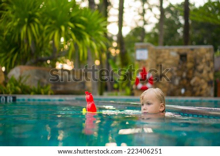 Adorable girl stay near pool side and play with toy boat in pool at tropical beach resort - stock photo