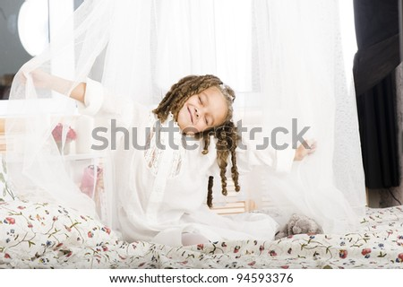 Adorable girl stretching on the bed - stock photo