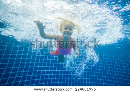 Adorable girl swim underwater after jumping into pool - stock photo