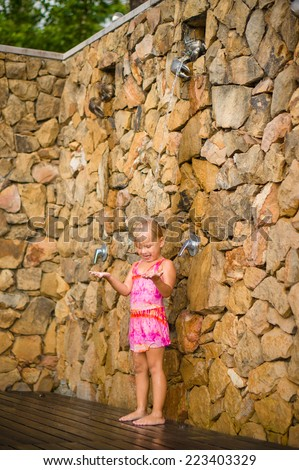 Adorable girl take shower after pool swim at tropical beach resort - stock photo