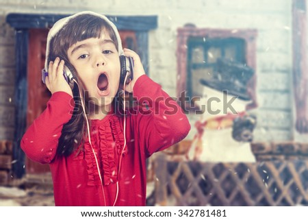 Adorable girl wearing a Santa hat listening to music and singing Christmas carols. Cross processed image with shallow depth of field - stock photo