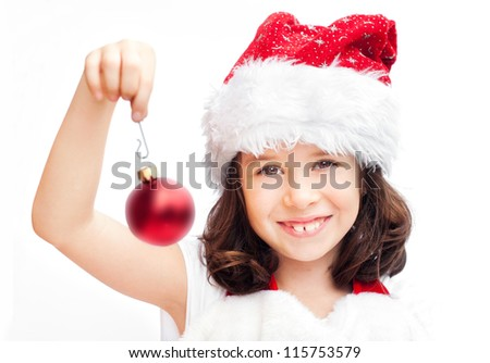 Adorable girl wearing Santa Claus hat with a Christmas ball - stock photo