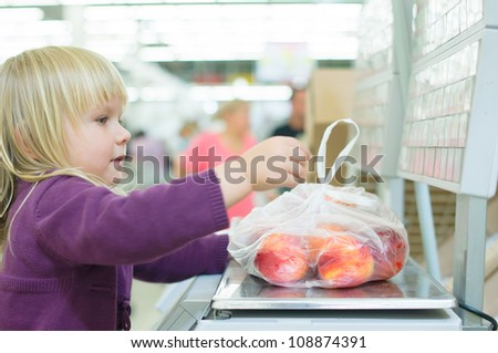 Adorable girl weighting fruits in supermarket - stock photo