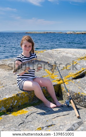 Adorable girl with big silver sea-trout - stock photo