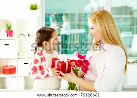 Adorable girl with bunch of beautiful tulips and giftbox giving them to her mother - stock photo