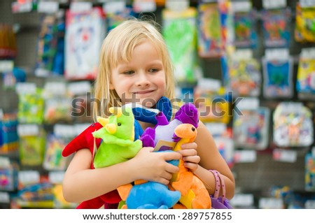 Adorable girl with bunch of plush toys in supermarket
