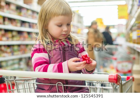 Adorable girl with decoration flower in shopping cart in supermarket