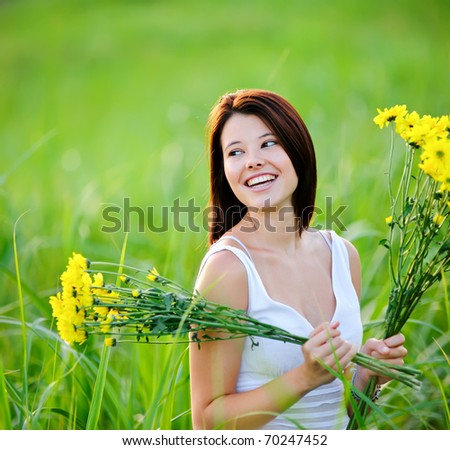 Adorable girl with flowers poses in a field during summer afternoon. - stock photo
