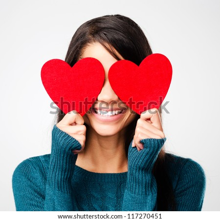 adorable girl with valentines day heart showing love fun affection portrait on grey background - stock photo