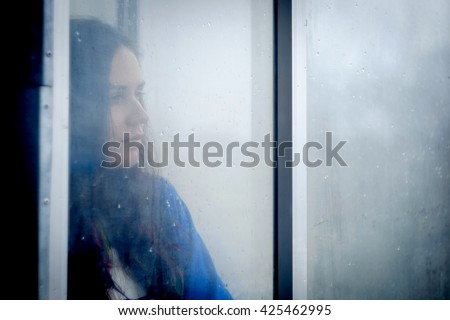Adorable girl (woman) staying near the window and looking on raindrops, indoors. A girl looks out the window. Vintage color. Unfocusing and foged window. Blue color. - stock photo