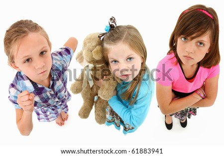 Adorable group of angry 7 year old girls over white background looking up towards camera.  Top view over white background. - stock photo