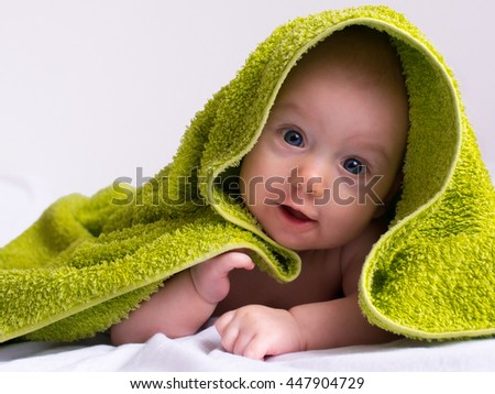Adorable half-year baby girl in a green towel. - stock photo