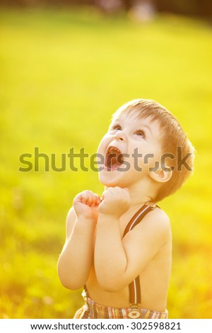 Adorable happy boy looking up and rejoining - stock photo
