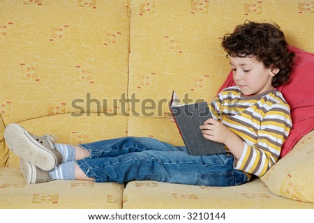 adorable happy boy reading in the armchair of your house