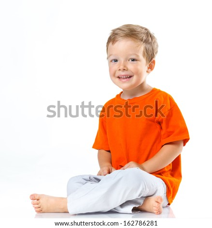 Adorable happy boy sitting on the floor in studio. Isolated of white background. - stock photo
