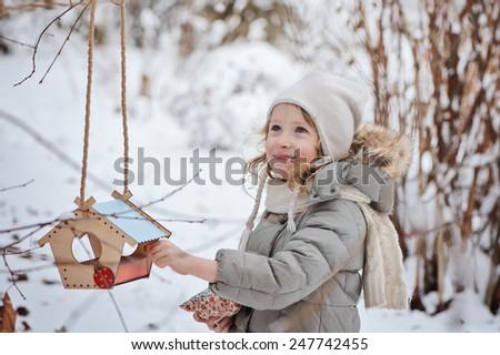 adorable happy child girl with bird feeder in winter garden - stock photo