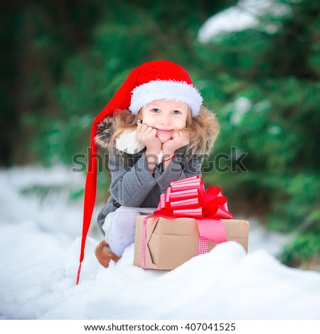 Adorable happy girl with christmas box gift in winter outdoors on Xmas eve - stock photo
