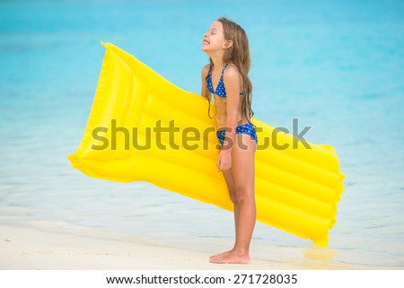 Adorable happy girl with inflatable air mattress on white beach - stock photo