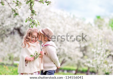 Adorable happy kids outdoors on spring day in beautiful blooming garden, little boy kissing a girl - stock photo