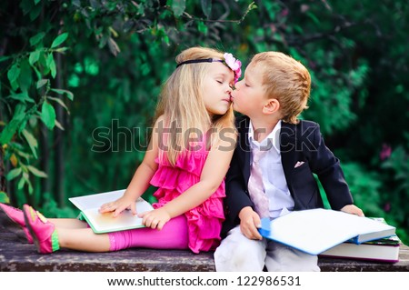 Adorable happy kids outdoors on summer day, little boy kissing a girl - stock photo